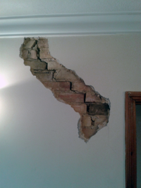 Crack in wall repaired with plaster